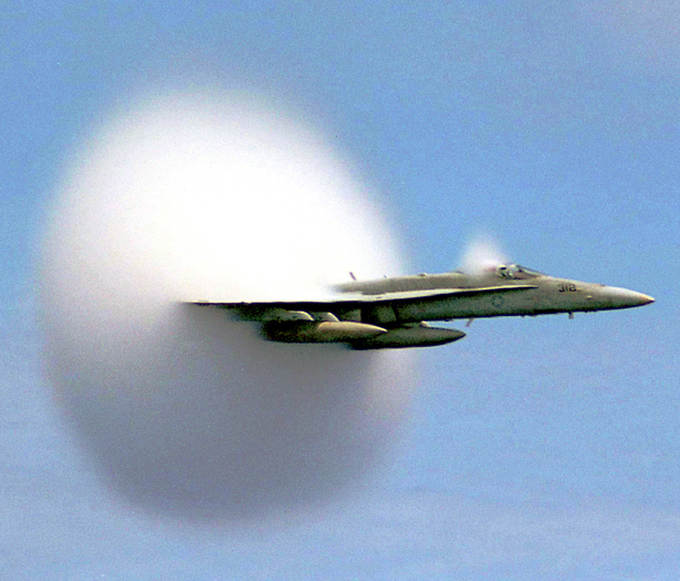As a work of the U.S. federal government, this image is in the public domain. Rapid condensation of water vapor due to a sonic shock produced at sub-sonic speed creates a vapor cone (known as a Prandtl–Glauert singularity), which can be seen with the naked eye